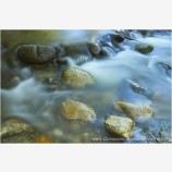 Silky Water and Shiny Rocks Stock Image